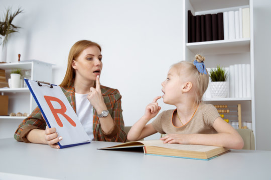 Speech therapy concept. Patient kid with female therapist training pronunciation