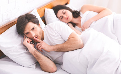 Man cheater talking privately on cellphone in family bed