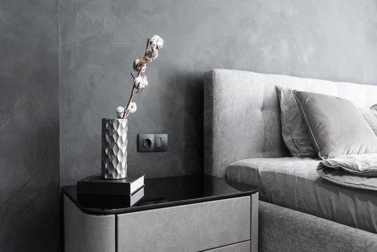 Stylish bedside table with dark book and vase with dried cotton branch on it. Interior details.