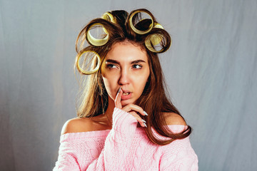 The portrait beautiful girl in hair curlers isolated on grey
