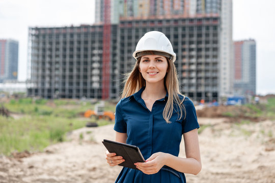 Female construction engineer. Architect with a tablet computer at a construction site. Young Woman look in camera, building site place on background. Construction concept