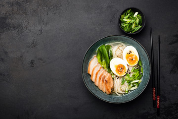 Asian ramen noodle soup with chicken on black concrete background. Top view, copy space for text