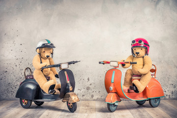 Retro Teddy Bear toys in helmets with goggles sitting on old children's pedal scooters from 60s front loft concrete wall background. Kids race competition concept. Vintage style filtered photo