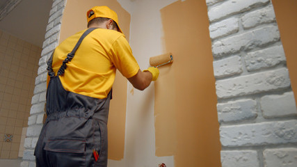 Worker painting wall with paint roller. Builder paints the wall in brown color. Building,...