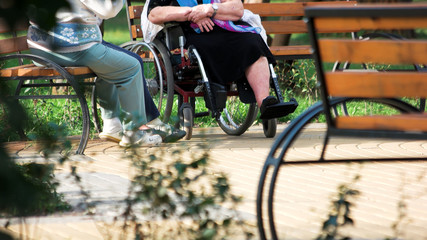 Old people talking sitting on bench outdoors. Disabled senior woman having coversation with her friends in the park.