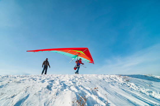Hang glider pilot ready to take off from mountain withhis bright wing.