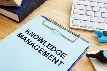 Knowledge management concept. Clipboard and books on table.