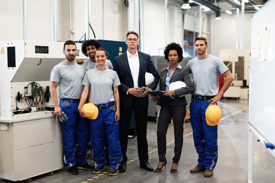 Portrait of company leaders and their employees in industrial plant.