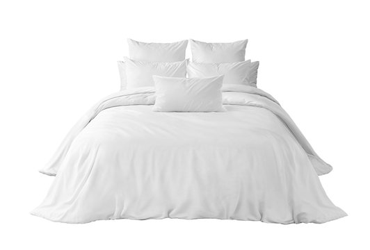White bedlinen on a white bed isolated. Bedroom with bed and linen. Bed with pillows and duvet isolated.