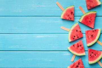 Watermelon triangles on wooden sticks, blue wood background