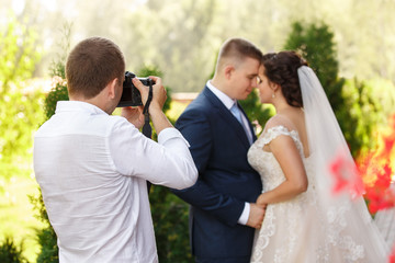 Wedding photographer takes pictures of the beautiful bride and groom outdoors