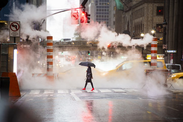 Tuinposter New York TAXI A woman with an umbrella and red high heels shoes is crossing the 42nd street in Manhattan. Cars and steam coming out from from the manholes in the background. New York City, Usa.
