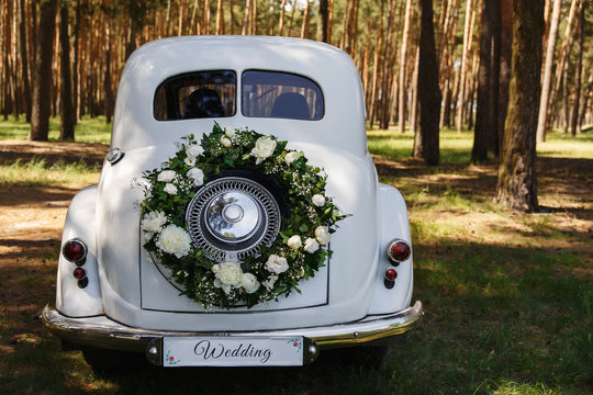 """Wedding car with a decoration in the form of a wreath and the word """"Wedding"""""""