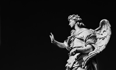 Angel statue holding the Nails of Jesus Cross. A 17th century baroque masterpiece at the top of Sant'Angelo Bridge in the center of Rome (Black and White with copy space)