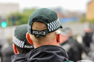 Police officers stand guard at a public event, wearing baseball caps.