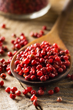 Pink or rose brazilian red peppercorns (schinus terebinthifolius) in wooden spoon on rustic wooden table background