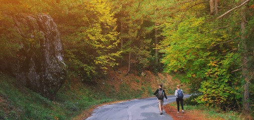 Rear view of young couple walking on road through woods with backpacks. Man and woman hiking in forest. Active adventure, travel, tourism, hike and people lifestyle concept. Beautiful forest nature.