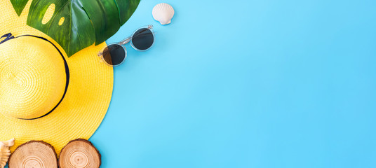 summer blue banner with yellow hat ,sunglasses,seashell and monstera leaf on blue background top view. Fotomurales