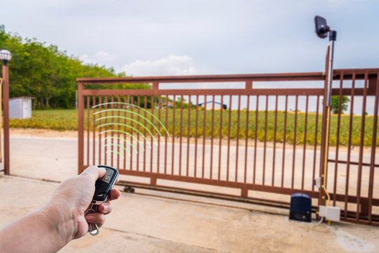 Signal of remote control when person open automatic gate at house system.