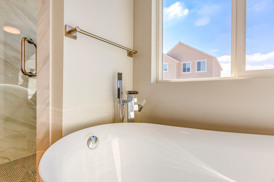 Bathtub and separated shower inside the bathroom with towel rod on the wall