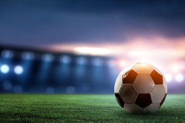 Full night football arena in lights with ball close up