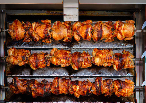 At a stall on a Spanish weekly market, chicken is prepared. They are crispy, fried, and rotate on several skewers on top of each other until they are ready for sale.