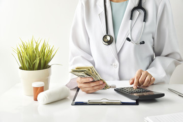Medical fee, Health insurance, Doctor holding dollar banknotes and calculate the examination charges, Money saving for healthcare services.