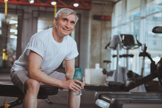 Cheerful senior man relaxing after working out at the gym, holding bottle of water, smiling joyfully. Happy healthy elderly man resting after exercising at sport studio, drinking water. Retirement, li