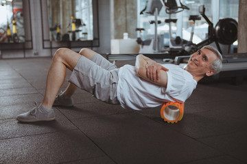 Cheerful senior man smiling to the camera, using foam roller on his back. Elderly sportsman relaxing his back muscles after working out at the gym. Massage, medical, health concept Wall mural