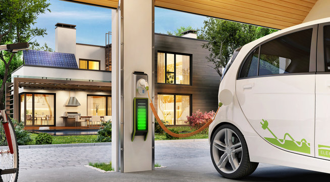Charging an electric car in the garage near the house. Modern house with solar panels on the roof.
