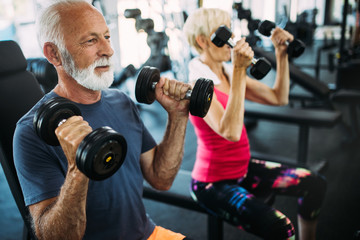 Mature fit couple exercising in gym to stay healthy