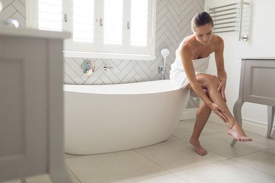 Beautiful woman applying lotion on her body in bathroom