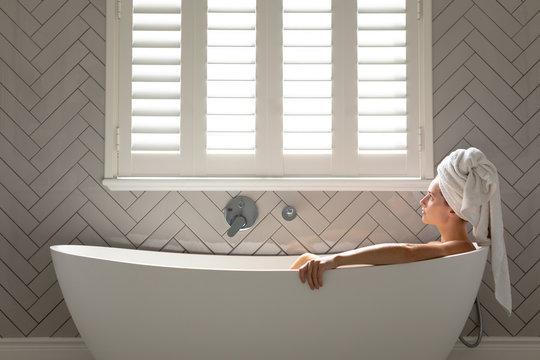 Thoughtful woman sitting in bathtub