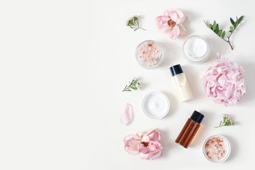 Photo sur Plexiglas Spa Styled beauty composition. Skin cream jar, tonicum bottle, roses, peony flower and Himalayan salt on white table background. Organic cosmetics, spa concept. Empty space, flat lay, top view.