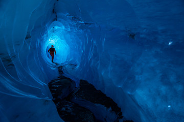 Guide inside an ice cave on a glacier in Alaska. Glacier caves are rare on teh Matanuska, but this one runs deep into the ice.