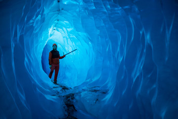 Wall Mural - Man inside a melting glacier ice cave. Cut by water from the melting glacier, the cave runs deep into the ice of the Matanuska Glacier in Alaska.