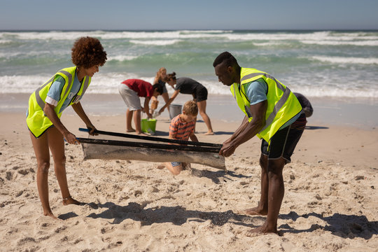 Volunteers cleaning beach on a sunny day