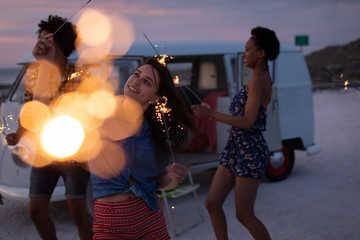 Group of friends enjoying at beach while they are standing near of camper van with sparkling bubble