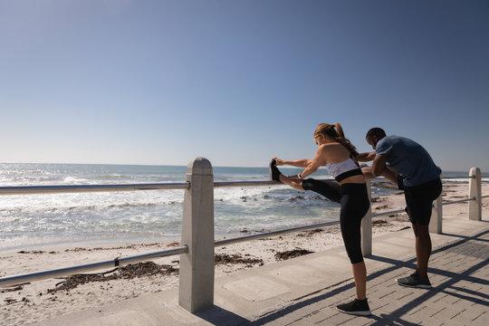 Young couple exercising near beach