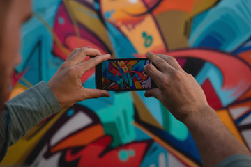 Graffiti artist capturing photo of painted wall