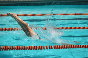 Young male swimmer jumping into water of a swimming pool