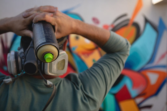 Graffiti artist holding painting spray in font of the wall