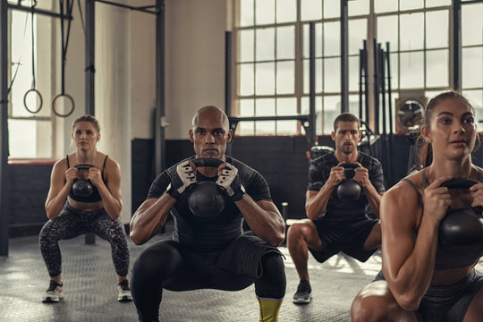 Fitness people squatting with kettlebell
