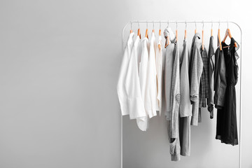 Rack with stylish clothes on light background