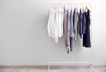 Rack with stylish clothes near light wall Wall mural