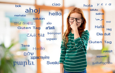 education, translation and learning concept - smiling red haired student girl in glasses and green...