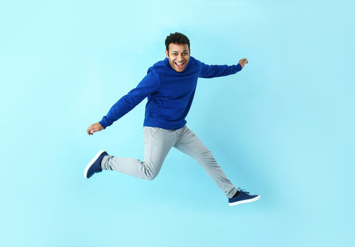 Handsome jumping man on color background