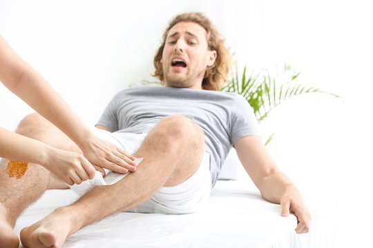 Man suffering from pain during wax epilation of legs in beauty salon