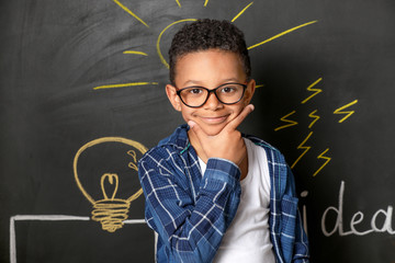 Thoughtful African-American boy near drawn light bulb on dark wall