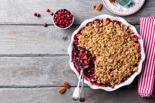 Cranberry crumble, crisp in a baking dish. Wooden background. Top view. Copy space.